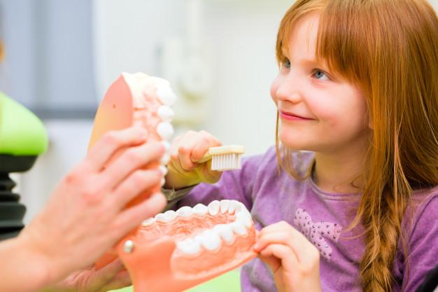 dentista-explicando-nina-limpiando-dientes_79405-1189